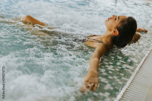 Canvas Print Young woman relaxing in the whirlpool bathtub at the poolside