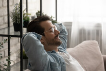 Side Head Shot View Calm Serene Young 30s Man In Eyeglasses Resting On Cozy Sofa With Closed Eyes And Folded Behind Head Hands, Daydreaming Sleeping Alone Or Visualizing Positive Future At Home.