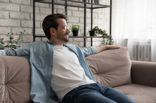 Tela Smiling young handsome man in glasses relaxing on comfortable couch, breathing f