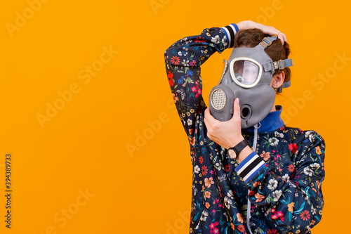 Foto Stylish strange woman in respirator posing over orange background