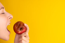 The Girl Bites A Rotten Apple With A Worm On A Yellow Background. Expired Products, Junk Food