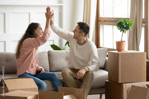 Fototapeta Happy wife and husband sit on couch near heap of belongings in boxes, giving hig