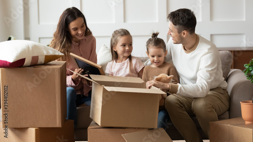 Obraz na plátně Family with 6s kids moved to new house sitting on couch in living room unpacking personal belongings from cardboard boxes chatting enjoy relocation day