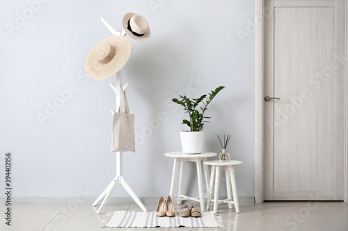 Stylish interior of modern hall with tables and clothes hanger