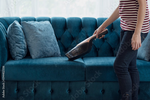 Obraz Woman housewife vacuuming furniture in a house with a hand-held portable vacuum cleaner - fototapety do salonu