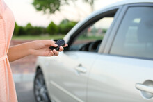 Young Woman Using Car Key Fob Outdoors