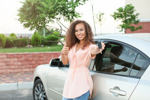 African-American Woman With Car Key Fob Showing Thumb-up Outdoors
