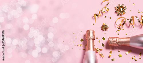 Fotografia Long wide Christmas and New Year's banner with rose Champagne bottles, golden decorations and bokeh lights on pink pastel background