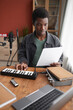 Leinwandbild Motiv Vertical portrait of young African-American musician composing music in home recording studio