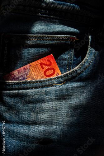 Obraz Twenty Swiss francs paper note in jeans pocket. - fototapety do salonu