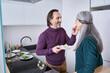 Leinwandbild Motiv Man feeding with cheese brie his grey haired wife