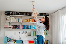 Woman Changing Bulb In House, Sweden
