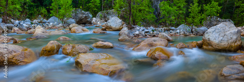 Fotomural small river rushing over a stones in a mountain canyon