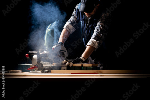 Leinwand Poster Carpenter working on woodworking machines in carpentry shop
