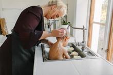 Mother Washing Baby In Kitchen Sink, Sweden