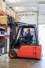 Woman Driving Forklift Truck In Warehouse, Sweden