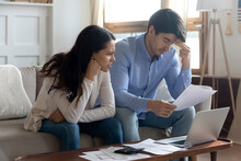 Falling Behind With Rent. Concerned Worried Young Married Couple Sitting On Sofa At Home Office Studying Paper Letters From Bank Informing About Debt Bankruptcy Financial Loss Unprofitable Investment