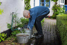 Man Filling Watering Can, Denmark