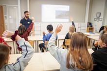 Children Raising Hands In Clas...