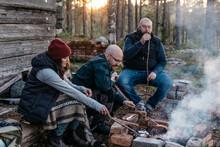 People Preparing Sausages Over Log Fire, Sweden