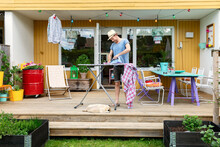 Man Ironing Clothes On Patio, ...