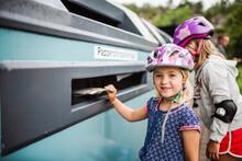 Girl Putting Rubbish Into Recycling Bin, Sweden