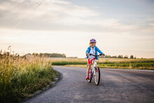Girl Cycling On Country Road, ...