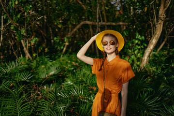 woman tourist wearing sunglasses hat exotic jungle tropics green leaves fresh