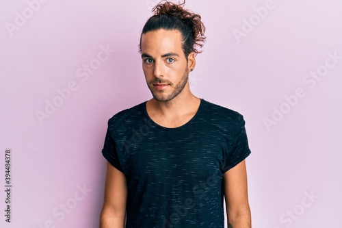 Carta da parati Young handsome man with long hair wearing casual clothes with serious expression on face
