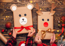 Children Hold Creatively Wrapped Christmas Gifts In The Shape Of A Teddy Bear And A Deer. New Year And Christmas Concept. DIY Gift Wrapping