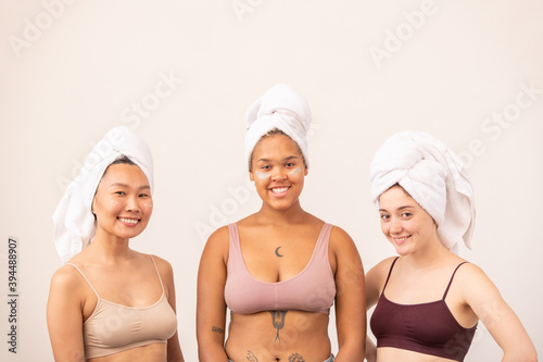 Cute Asian, African and Caucasian girls with soft towels on heads and tanktops