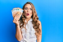Young Blonde Girl Holding Euro Banknotes Scared And Amazed With Open Mouth For Surprise, Disbelief Face