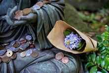 Close-up Of Statue With Flowers And Coins