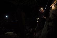 Man Climbing On Rock At Night