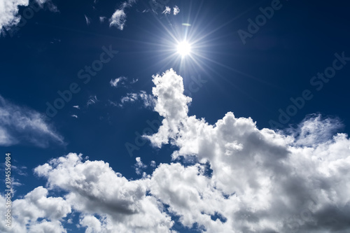 Niebieskie niebo i słońce między chmurami  - fototapety na wymiar