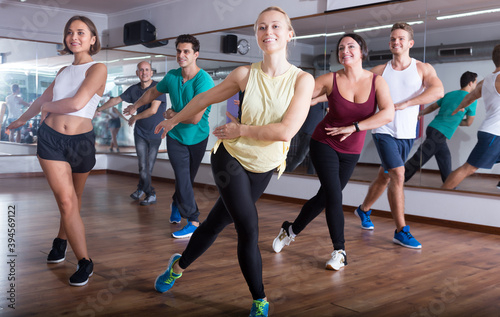 Fotografia, Obraz Glad positive people learning zumba steps in dance hall