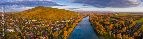 Tokaj, Hungary - Ultra wide aerial panoramic view of the small town of Tokaj with golden vineyards on the hills of wine region on a warm sunny autumn morning Fototapet