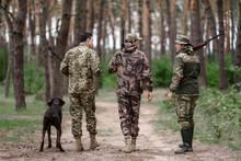 Men In Camouflage Hunters Walk Away By Path.