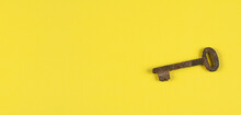 Old Rusty Key On A Yellow Background. Knowledge Concept