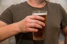 A Glass Of Beer In The Man's Hand. Holding A Glass To His Chest In A Khaki T-shirt On A White Background.