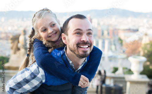 Cheerful father and daughter taking walk in city during sightseeing tour Fototapet