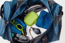 Close Up Shot Of Sports Bag With Swimming Gear For Men Isolated On Grey Background. Swim Goggles, Hat, Trunks, Towel And Bottle Of Water