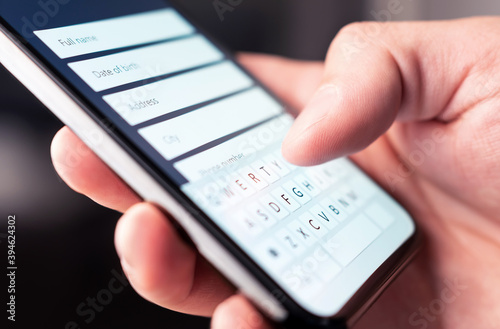 Online form to register personal info and data to web site with mobile phone. Person typing information to internet document, survey or questionnaire with smartphone. Customer registration to website. - fototapety na wymiar