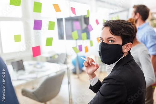Business Frau mit Maske im Brainstorming Workshop