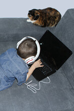 Kid, Boy In Headphones, Lies On A Sofa In Front Of An Open Laptop, Blank Black Screen, A Cat Sits Nearby And Looks, A Concept Of Children's Computer Security
