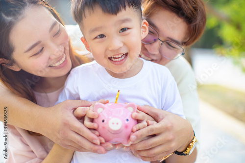 Fotografie, Obraz happy parent holding piggy bank and teaching son save money