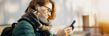 Young Woman With Wireless Headphones And Mobile Device Listening To Music Outdoor In Autumn Winter City