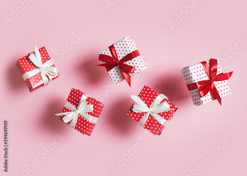 Polka dot pattern red gift box with ribbon falling on pink background