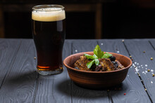 Grilled Pork Ribs With Fresh Parsley ,damson And Glass Of Dark Beer On Black Wooden Background