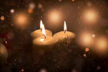 White Christmas Candles Are Burning, Green Fir Branches Are Lying Next To Them, Christmas Toys, Festive Highlights Of Garlands And The Flame Of Three Candles Give A Sense Of Celebration.